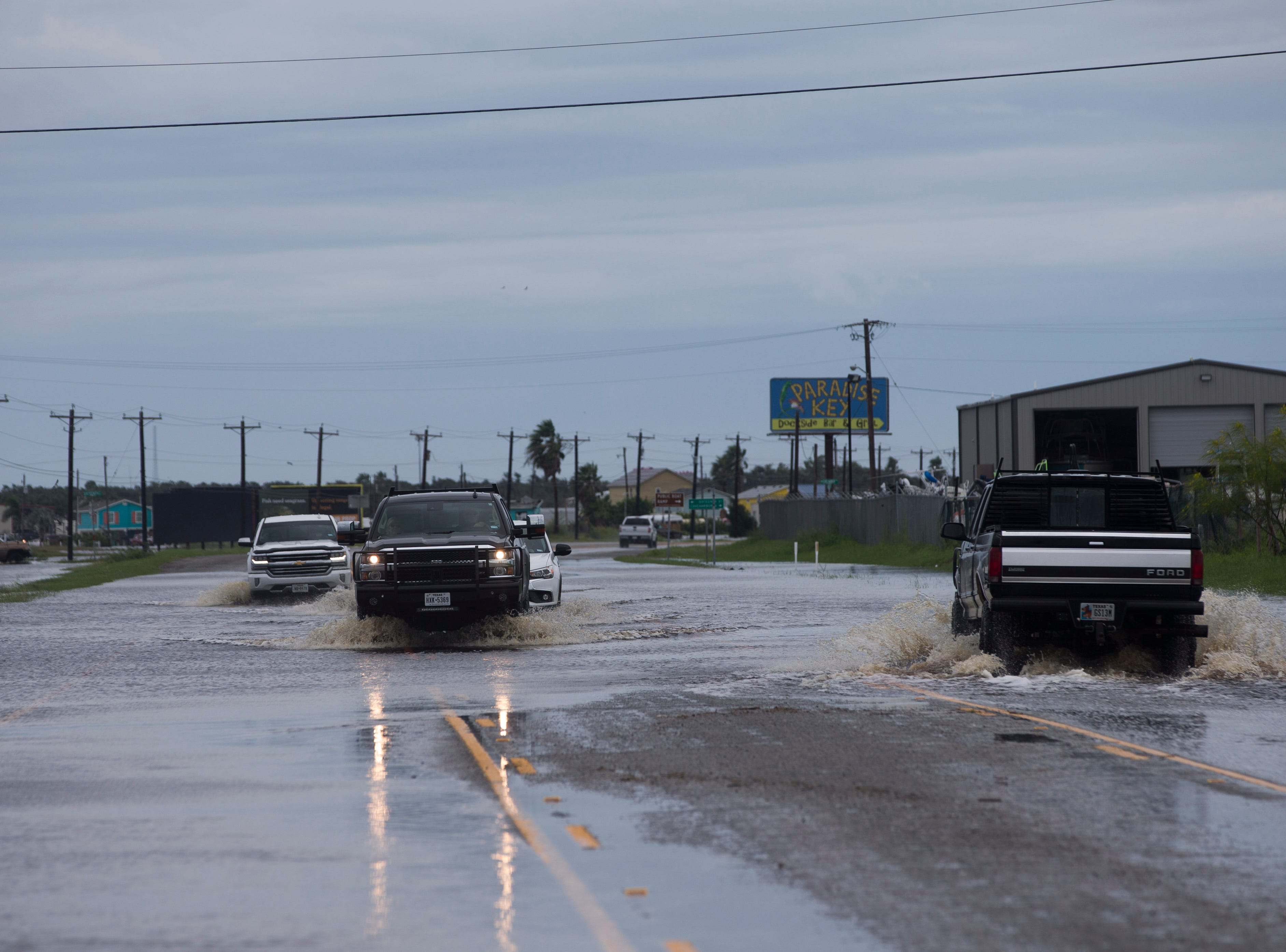 Vehicles drive through high water on Business State Highway 35 between Rockport and Aransas Pass on Saturday, Sept. 15, 2018.