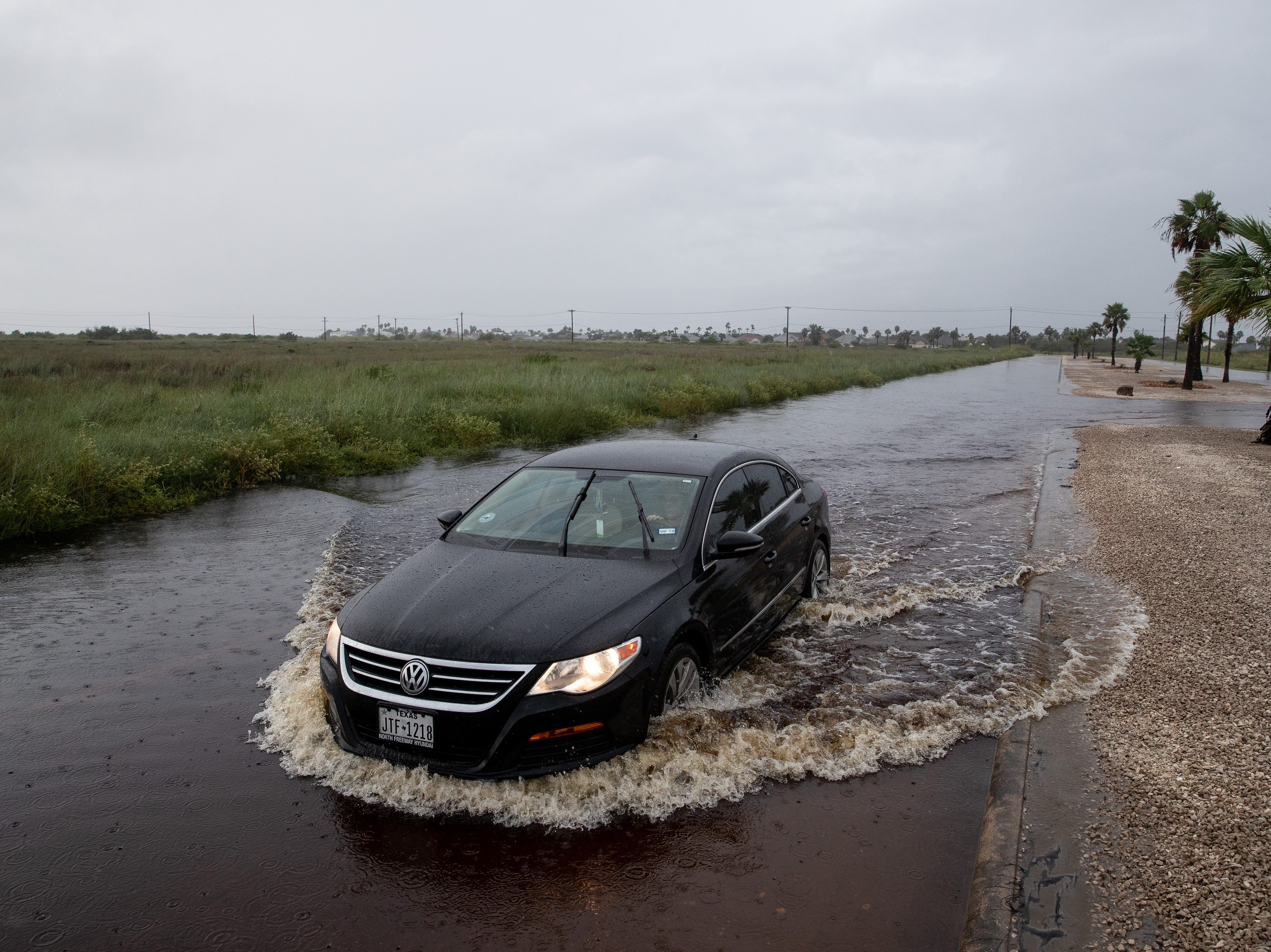 A car drives down a flooded Commodore Drive on North Padre Island in Corpus Christi as heavy rains fall on Saturday, Sept. 15, 2018.