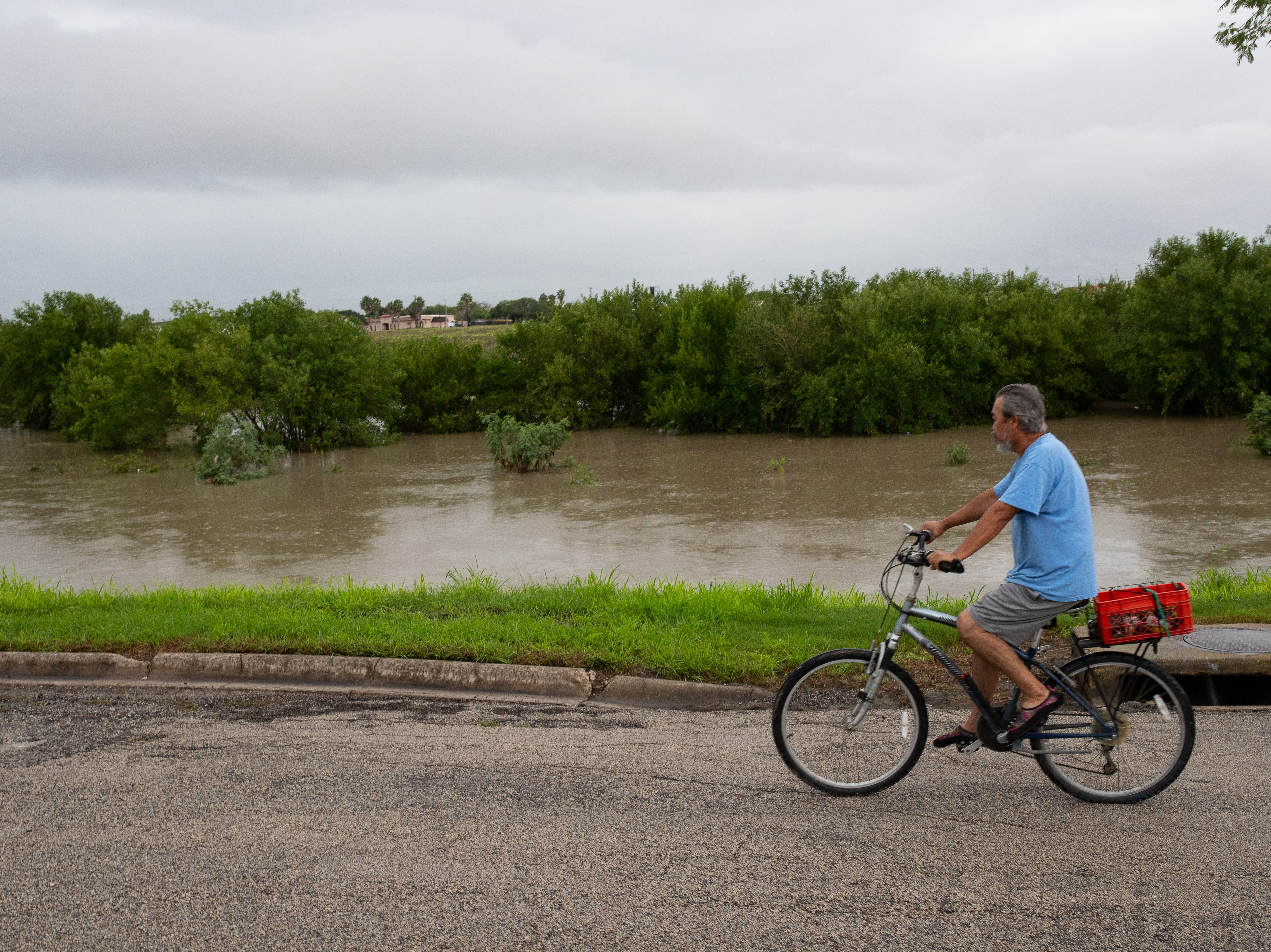 A man on a bike rides past an elevated La Volla creak next to the Las Colonias neighborhood on Saturday, Sept. 15, 2018.