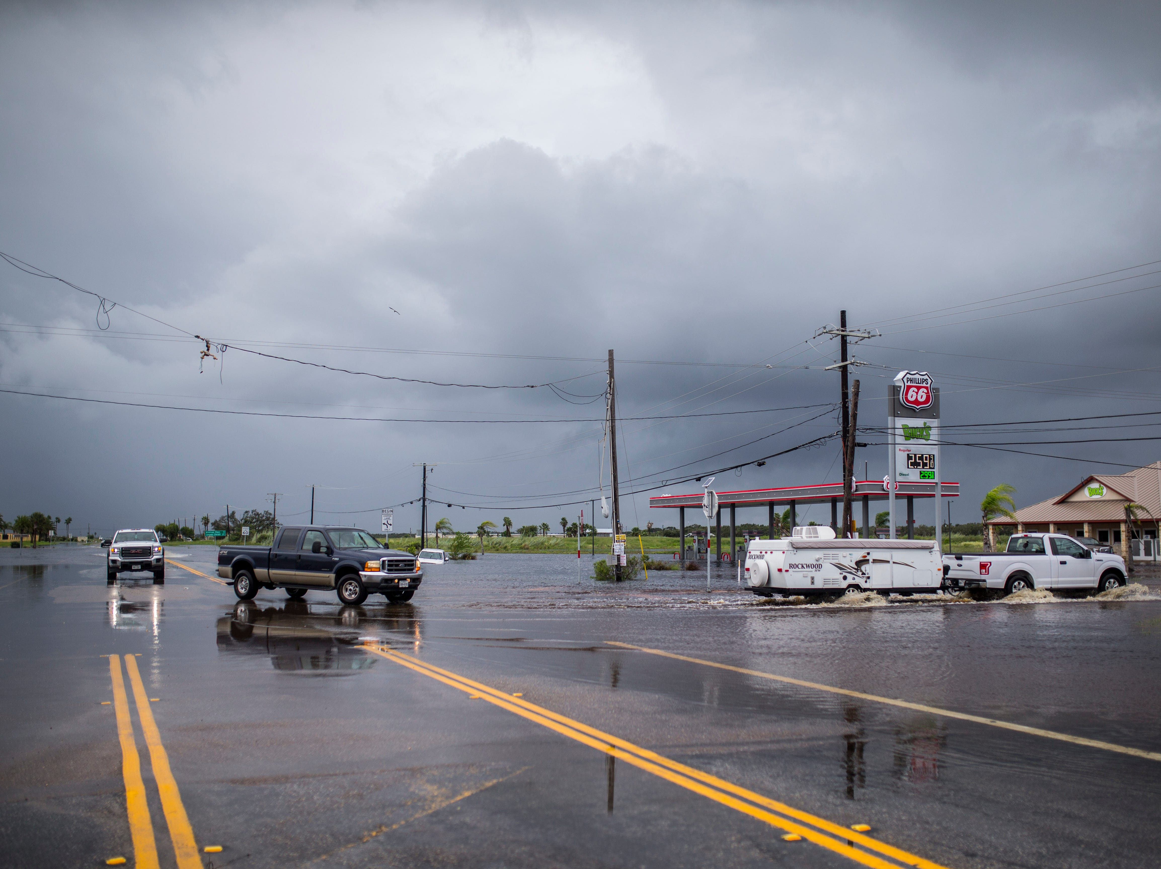 Vehicles drive through high water on Business State Highway 35 and State Highway 188 between Rockport and Aransas Pass on Saturday, Sept. 15, 2018.
