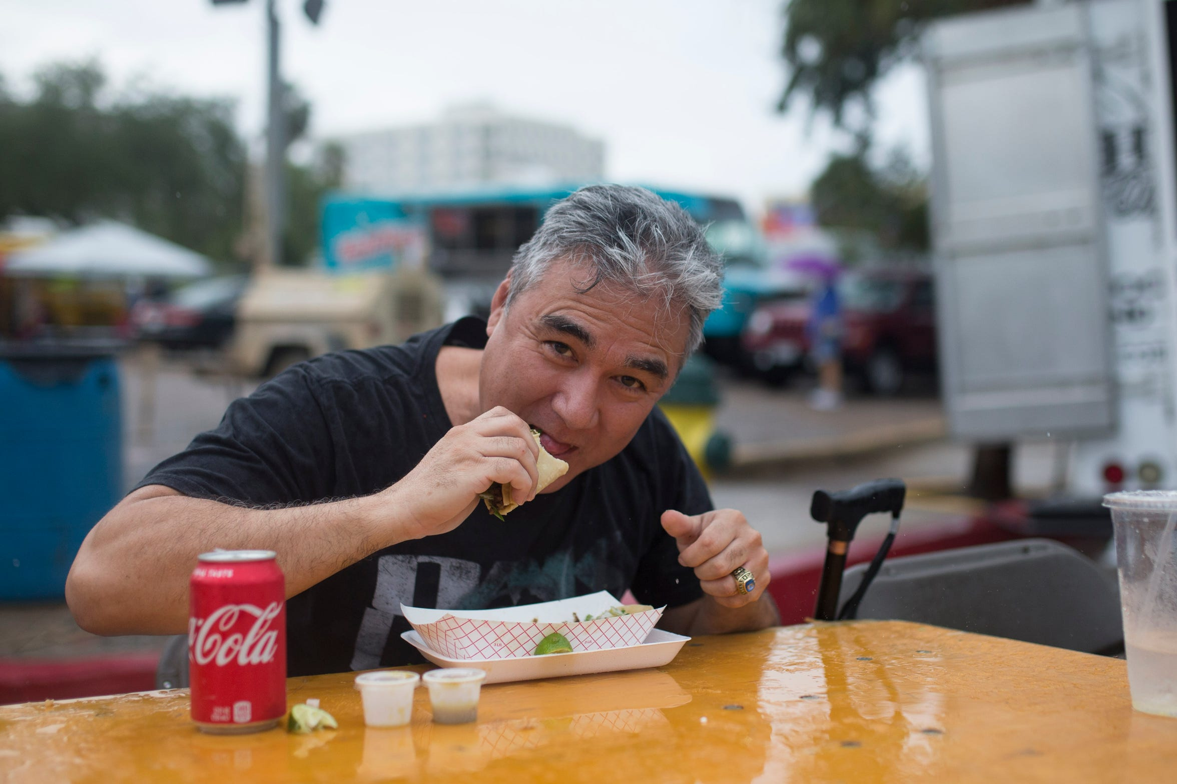 Kenneth Castro eats tacos in the rain at the Que Bueno Taco Fest in Corpus Christi on Saturday, Sept. 15, 2018.
