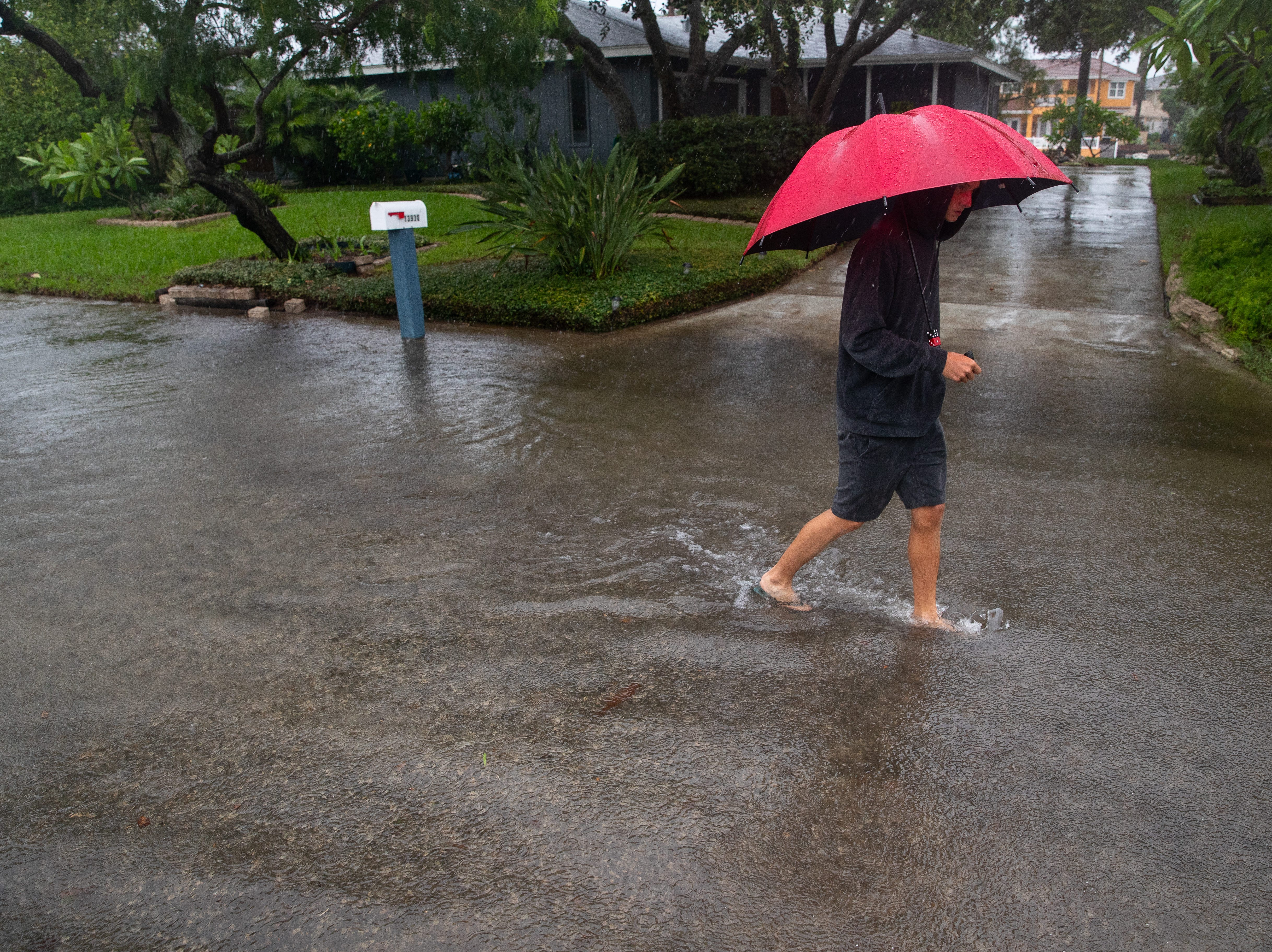 A person walks down a flooded North Cabana Street on North Padre Island in Corpus Christi as heavy rains fall on Saturday, Sept. 15, 2018.