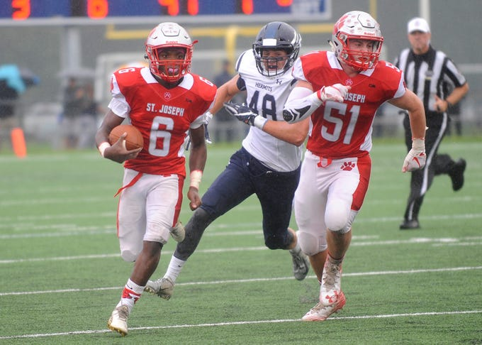 St. Joseph RB, Nate Johnson (6) runs the ball against St. Augustine while Bobby Hyndman (51) looks for a block. The Wildcats rolled past the Hermits 30-8 in Richland on Friday, September 14.