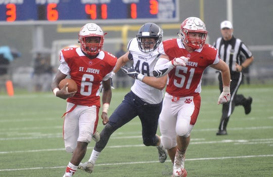 St. Joseph's Nate Johnson, one of four Wildcats to intercept a pass in the team's 30-8 win over St. Augustine on Friday, runs with Bobby Hyndman leading the way.