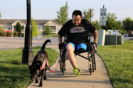 Hamilton County Commissioner Todd Portune walks his daughter's dog, Rebel, before getting ready for work, Friday, Aug. 31, 2018, at his home in Green Township, Ohio. In 2003, Portune was diagnosed with benign tumors in his spinal column, which eventually ruptured, and paralyzed him from the chest down.