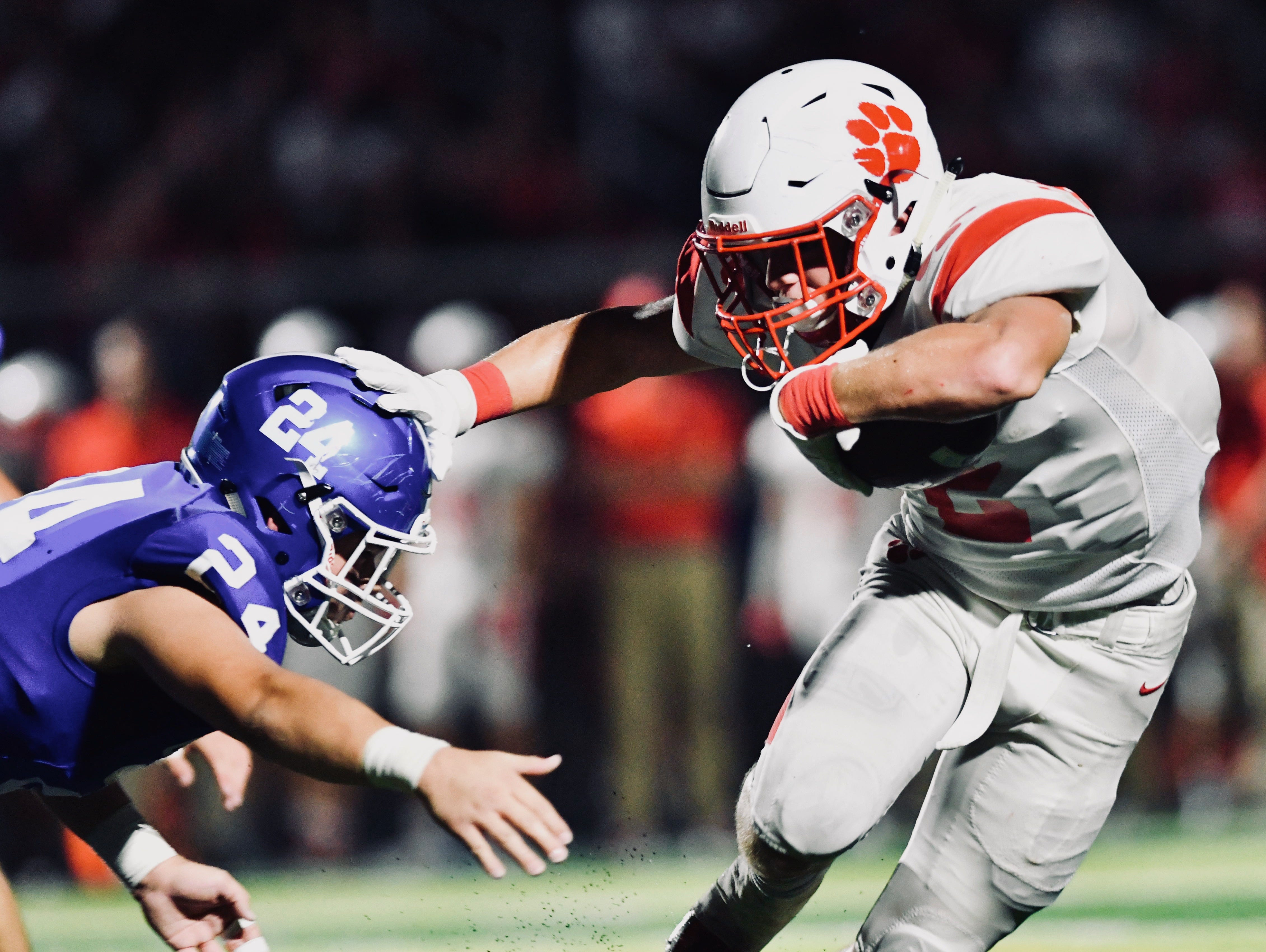 Beechwood's Logan Castleman lays a stiff arm on a Covington Catholic defender in the third quarter Friday, Sept. 14, 2018.
