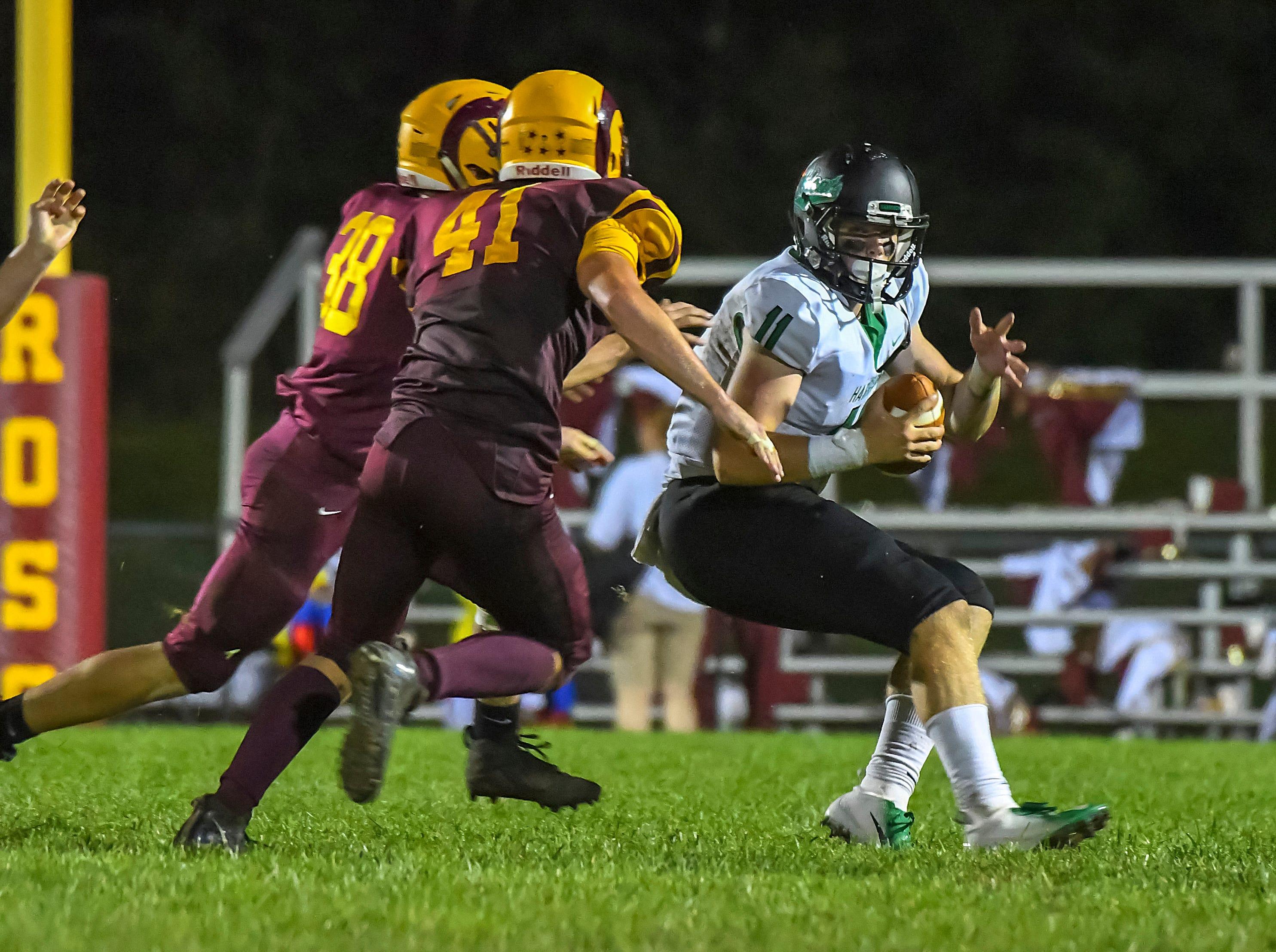 The Ross defense chases Harrison quarterback Connor Kinnett (11) out of the pocket, Ross High School, Friday, September 14, 2018