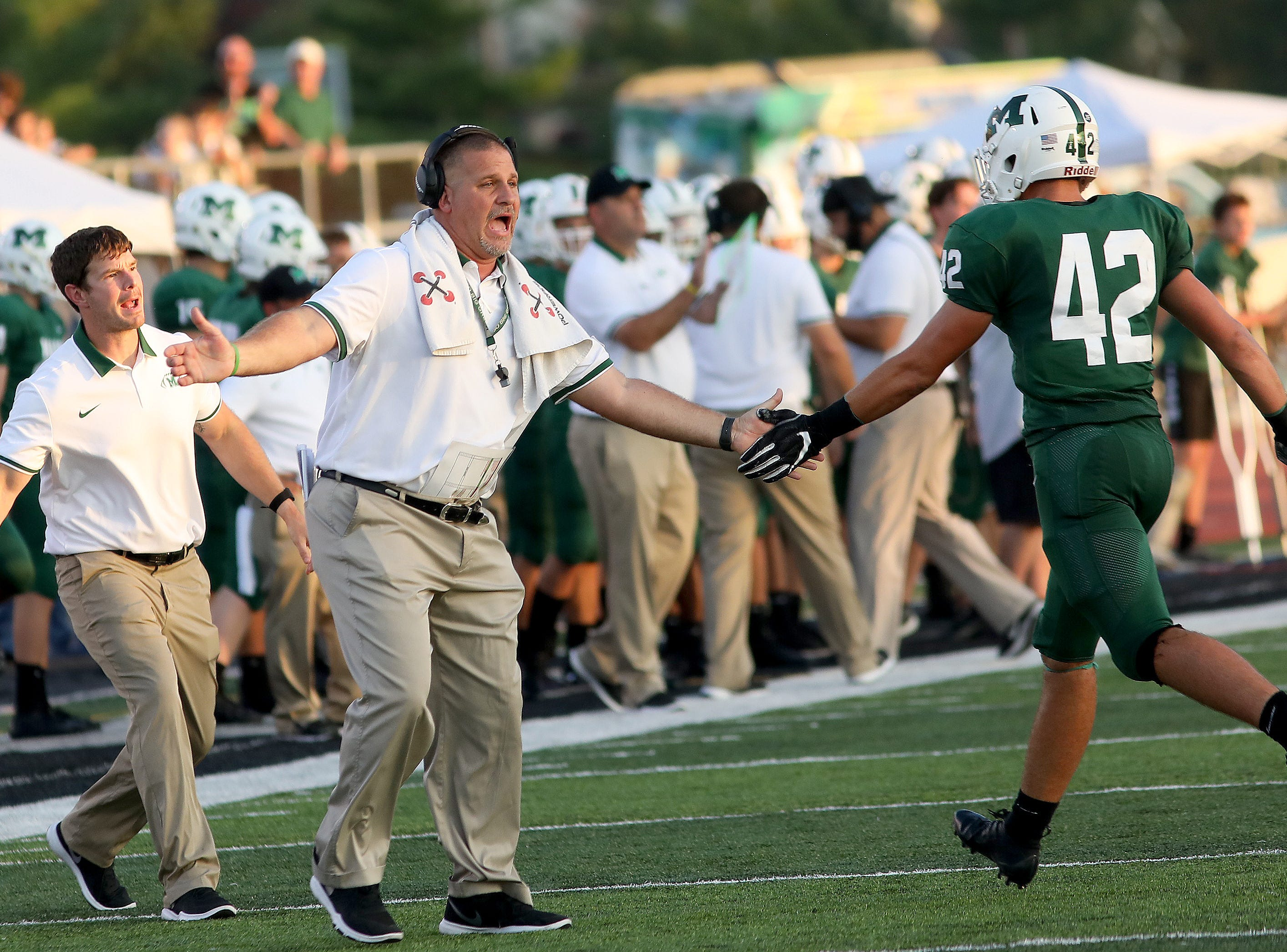Mason head coach Brian Castner celebrates with his team during  the Comets' football game against Sycamore, Friday, Sept. 14, 2018.