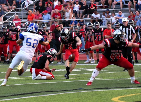 Placekicker Luke Lundberg (6) of Indian Hill lifts home a field goal out of the hold of Alex Lindberg to add to the Braves 2nd quarter lead, Sept. 14, 2018.