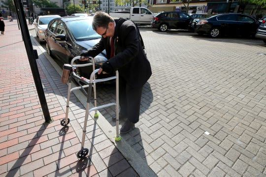 """Hamilton County Commissioner Todd Portune takes a step onto the sidewalk after arriving outside the county administration building, Friday, Aug. 31, 2018, in downtown Cincinnati. There are no curb ramps directly outside the front door, only on street corners, Portune said. """"The issue with people with disabilities continues to be, in terms of your protected classes, one that remains almost a stepchild in some respects of other protected classes."""""""