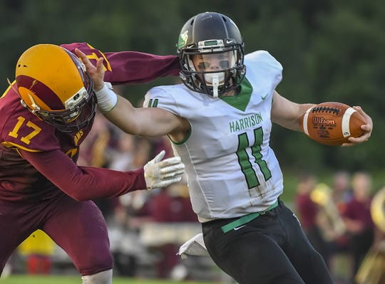 Harrison quarterback Connor Kinnett (11) stiff arms Ross defender Sean Lange (17), Ross High School, Friday, September 14, 2018