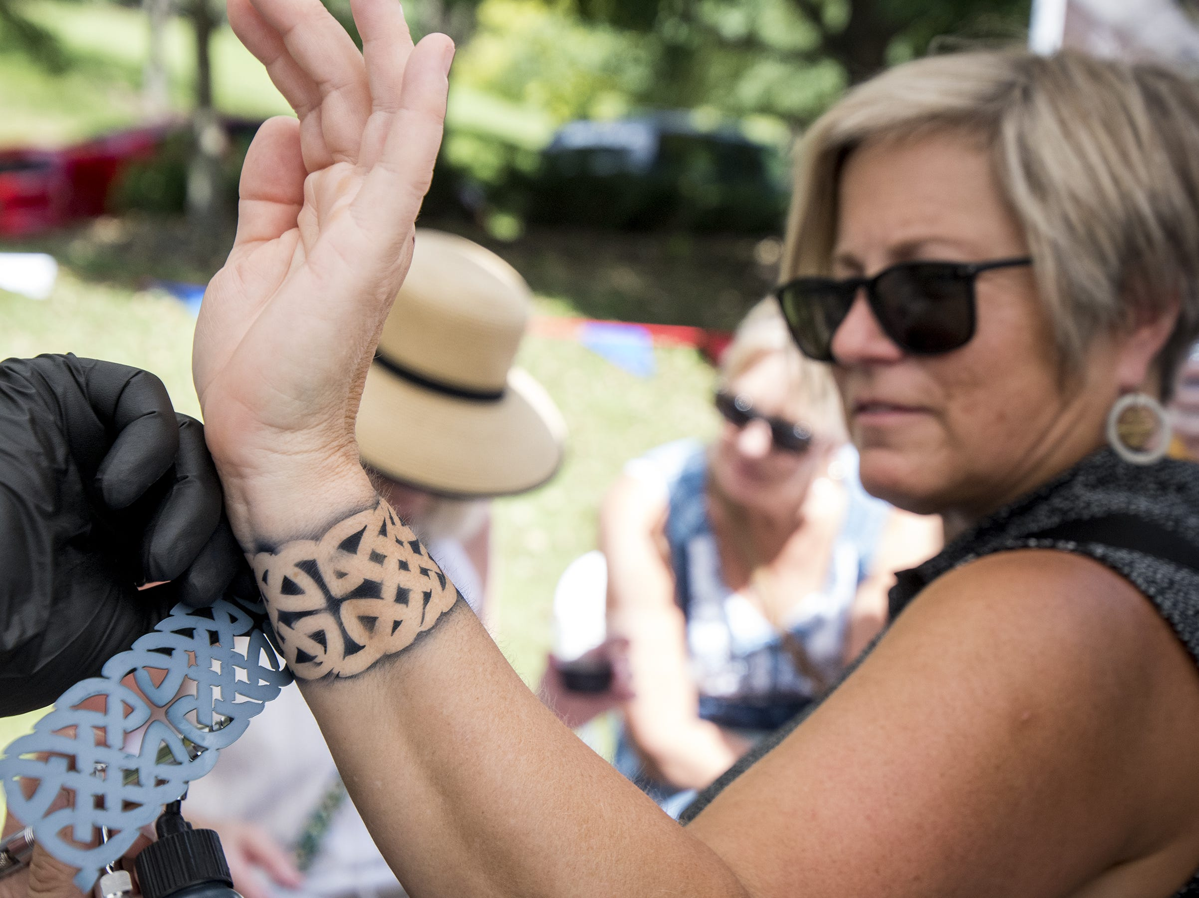 Dede Ackerman of Milford gets a airbrush tattoo at the Faces By Lisa booth during Fifty Fest at 50 West Brewing Saturday, September 15, 2018 in Cincinnati, Ohio. The family-friendly festival will have music and entertainment until midnight Saturday.