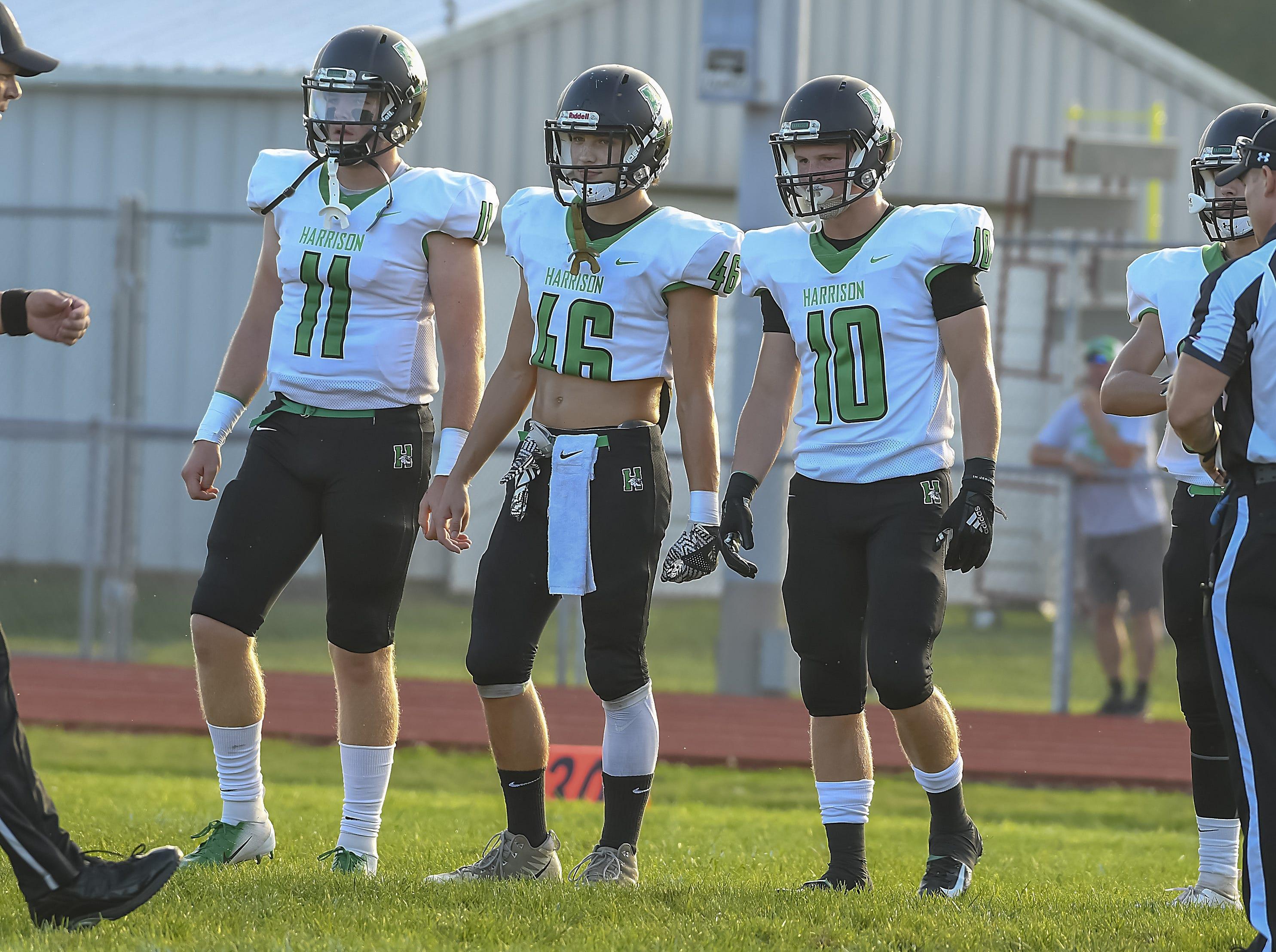 Harrison captains Connor Kinnett (11), Simon Shirley (46) and Levi Tidwell (10) walk out for the coin flip against Ross, Ross High School, Friday, September 14, 2018