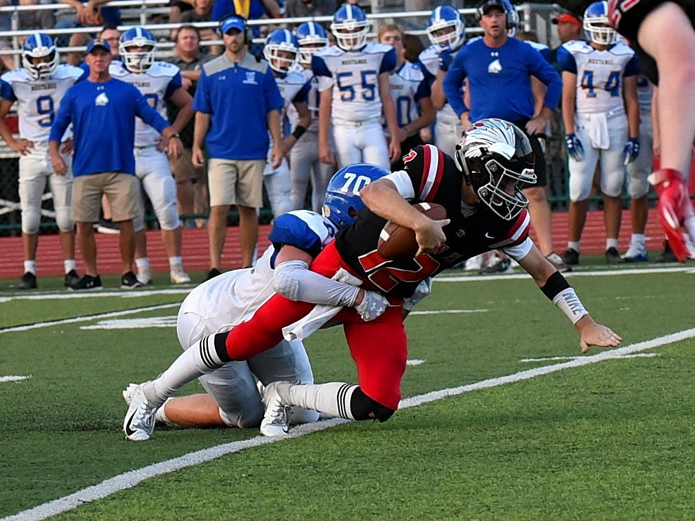 Indian Hill's Cole Dein (12) is sacked by Madeira's Trey Kanet (70), Sept. 14, 2018.