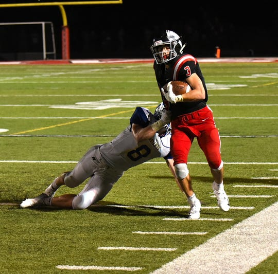 Tre Lopez III of Indian Hill runs out of the would-be tackle of Madeira's Nick Groene (8), Sept. 14, 2018.