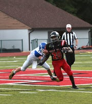 Vinnie Englert (11) of Madeira pulls down Indian Hill's John Mark Williams (20) before he can gain first-down yards, Sept. 14, 2018.