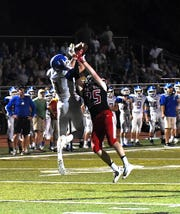 Lee Megois (1) of Madeira grabs an interception out of the hands of Indian Hill's Zack Osterhues (25), Sept. 14, 2018.