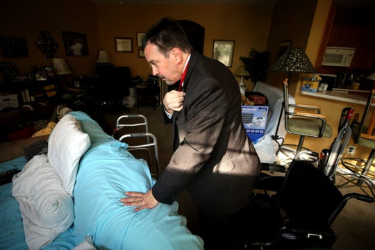 Hamilton County Commissioner Todd Portune leans on the couch where he sleeps while pinning a pin on his jacket, Friday, Aug. 31, 2018, at his home in Green Township, Ohio.