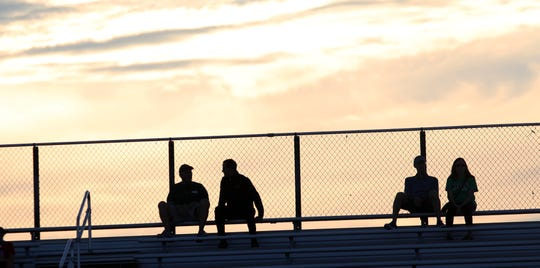 Fans sit at the top of the high school stadium as the sun sets before their team's game last September.