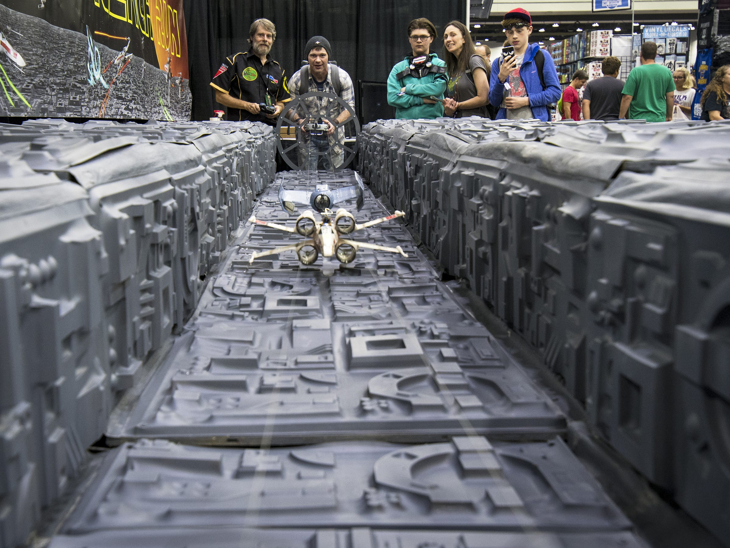 A guest flies an X-Wing model down a trench of the Death Star.