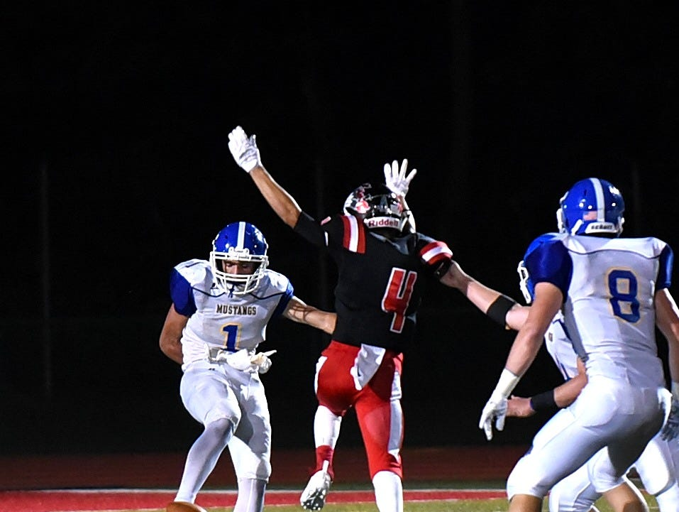Marc Bennett (4) of Indian Hill stretches out in attempt to block the punt of Madeira's Lee Megois (1), Sept. 14, 2018.