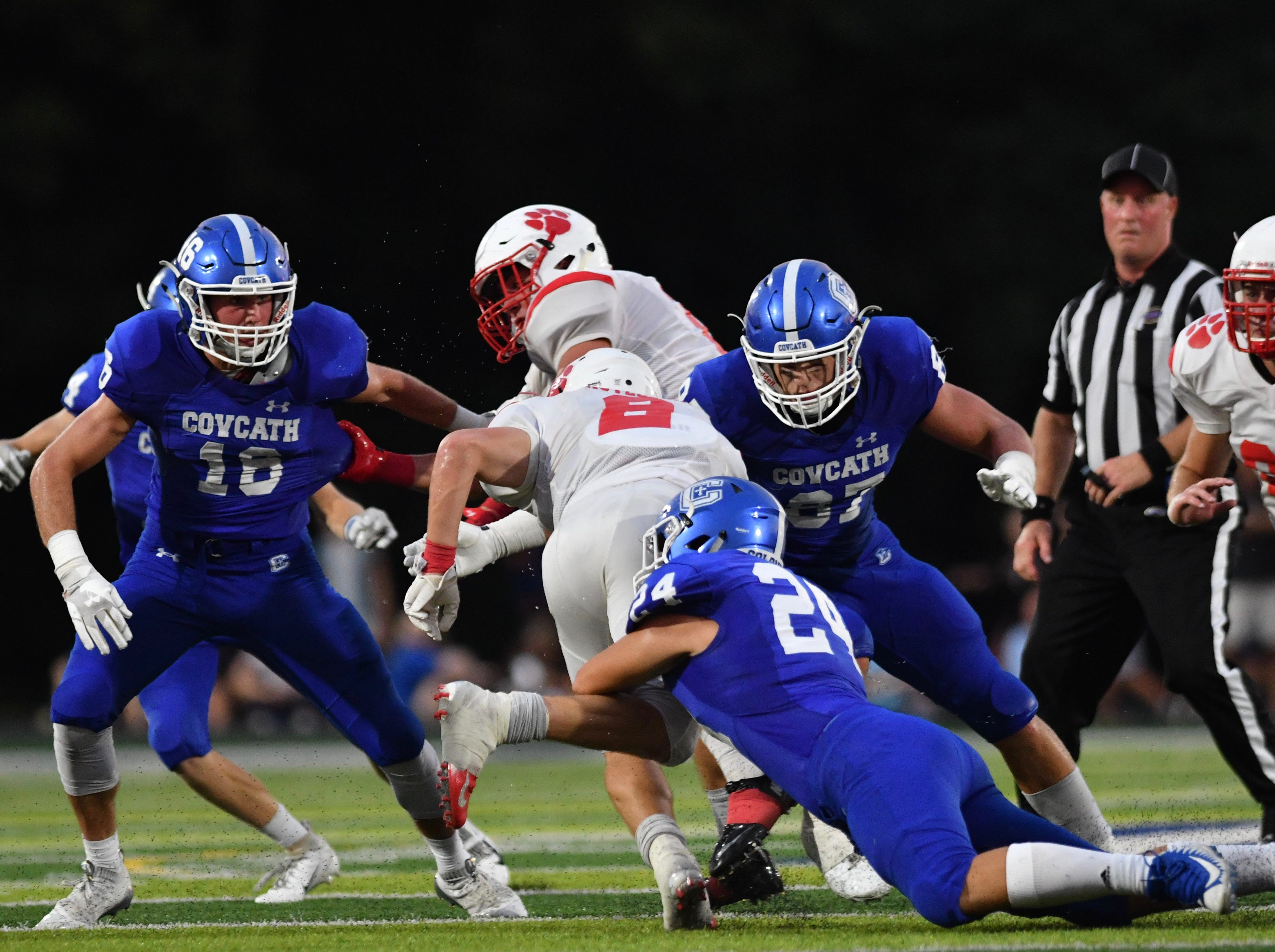 Beechwood's Josh Derry is tackled by a swarm of Covington Catholic defenders including Daniel Felix and Michael Mayer Friday, Sept. 14, 2018.