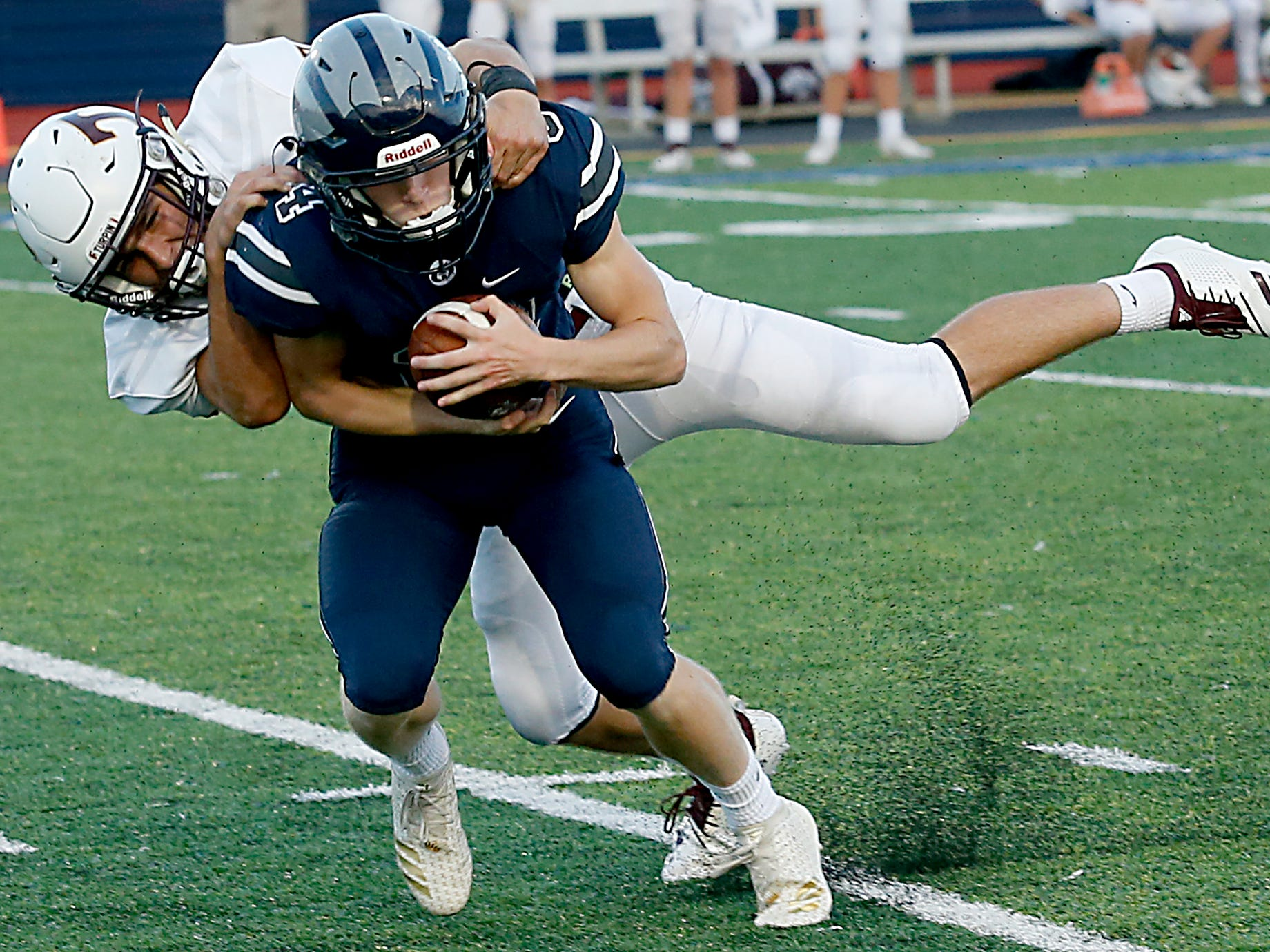 West Clermont's Ryan Cann hauls in a pass as Turpin's Sam Machenheimer pulls him down during their 2018 Skyline Chili Crosstown Showdown at West Clermont Friday, Sept. 14, 2018.