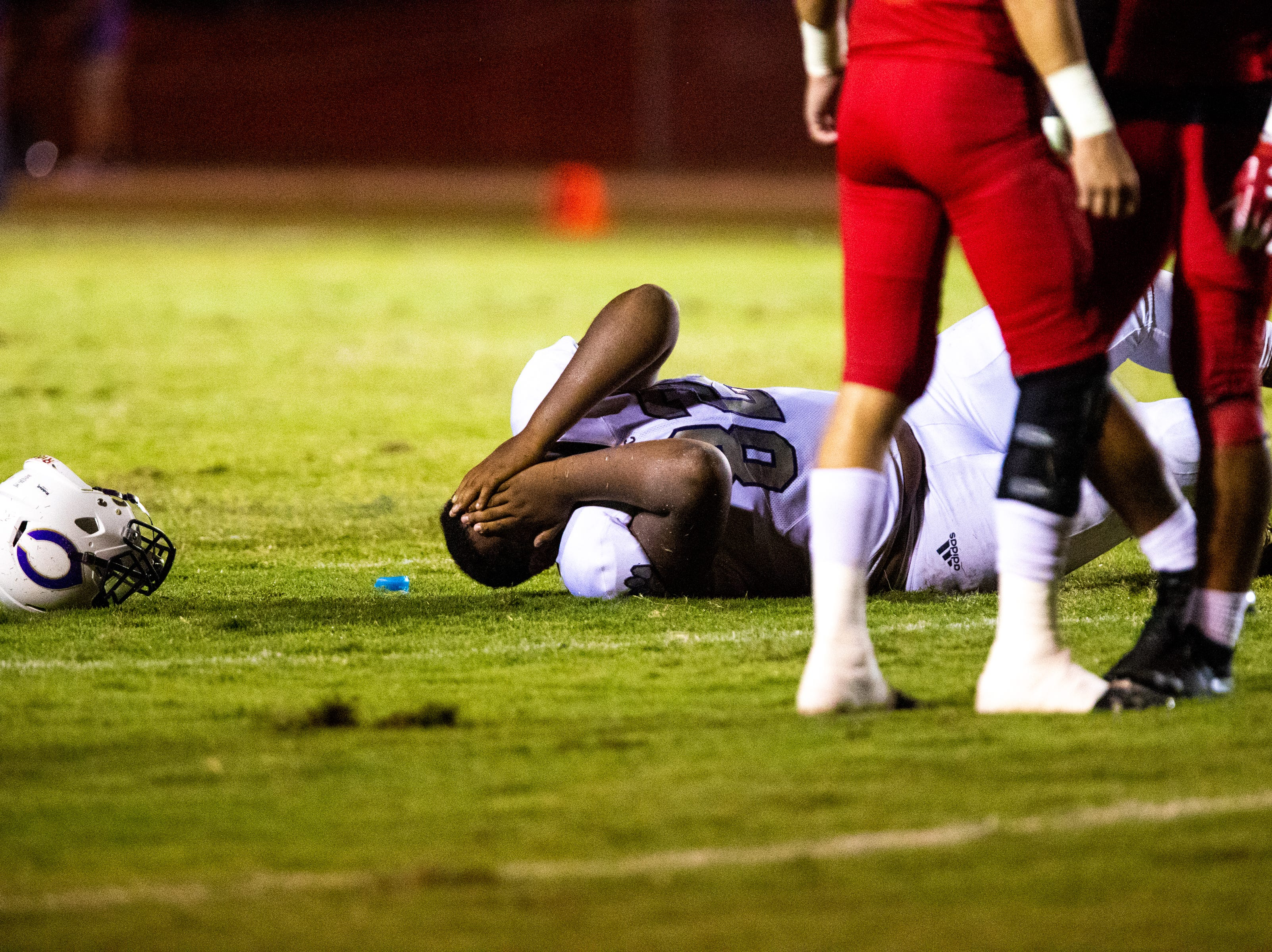 Khalil Smith (82) of Clarksville High covers his face after hurting his ankle during the second half at Henry County Friday, Sept. 14, 2018, in Paris, Tenn.