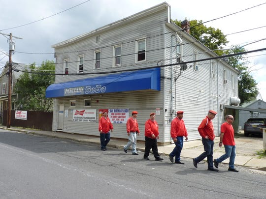 The Guardian Angels, led by Curtis Sliwa and Councilman Joe Lukac, walk pass Foxtails Lounge in Manville weeks after two men were arrested on weapons charges following an altercation near the strip club.
