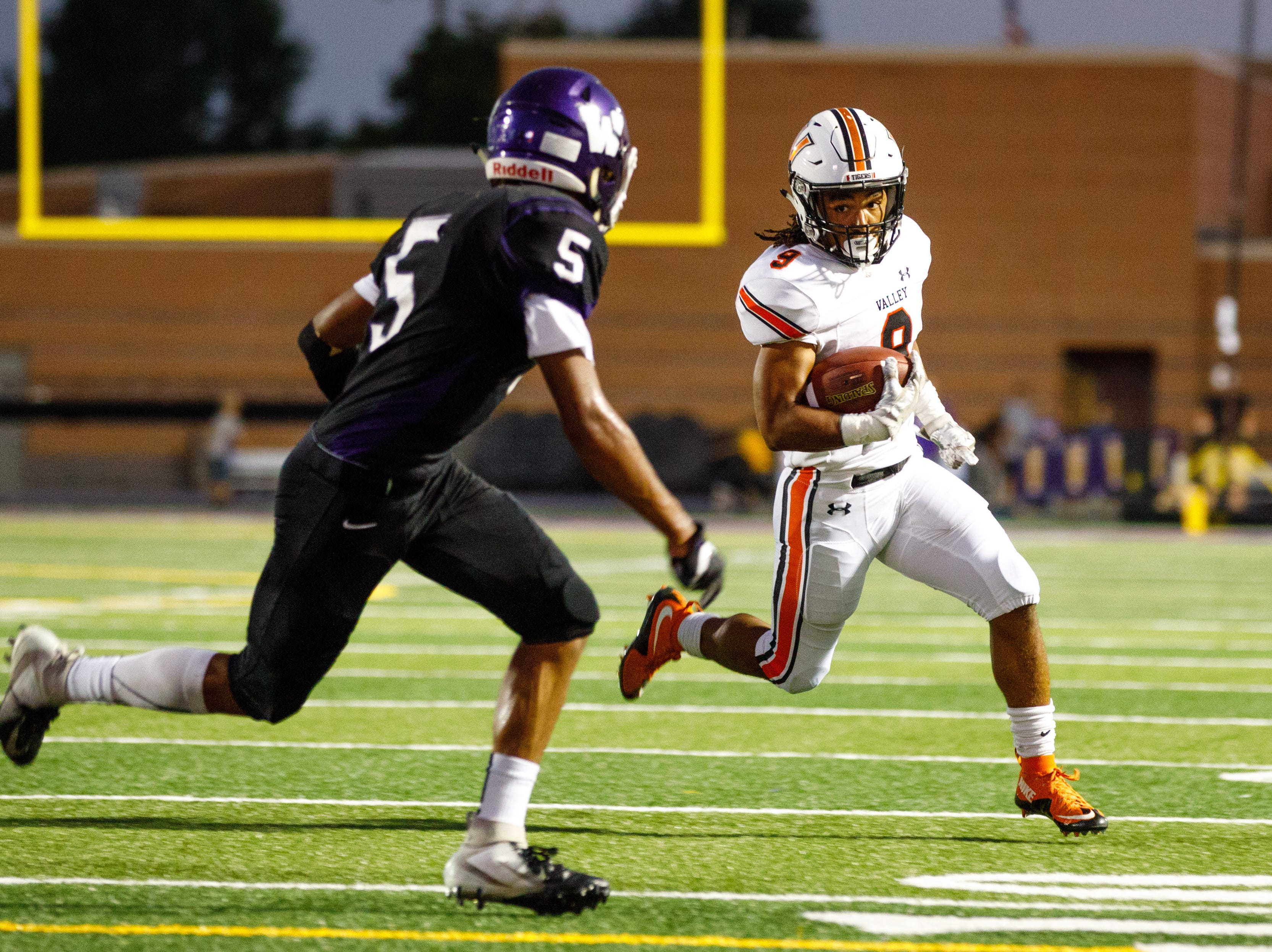 Valley High School's Creighton Mitchell (9) tries to run around Waukee's Aaron Smith (5) in the second quarter Friday, Sept. 14, 2018, at Waukee Stadium.