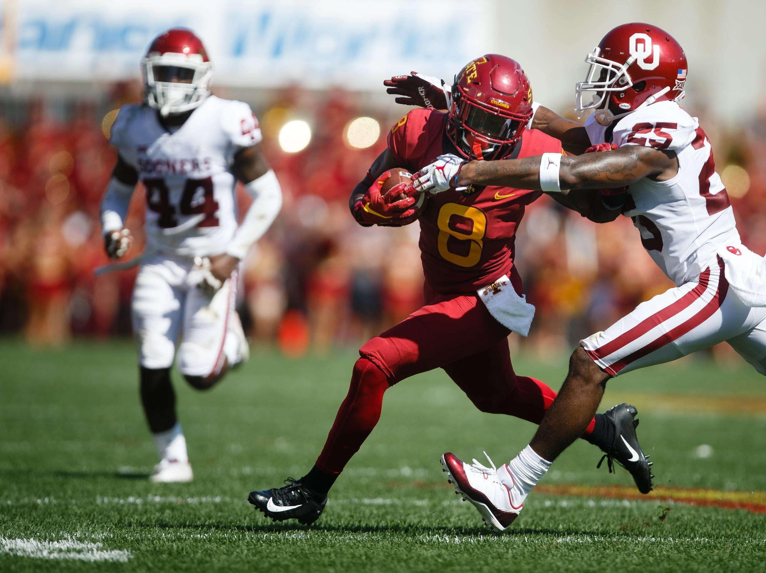 Iowa State's Deshaunte Jones (8) tries to get away from Oklahoma's Justin Broiles (25) during their football game at Jack Trice Stadium on Saturday, Sept. 15, 2018 in Ames. Oklahoma would go on to win 37-27.