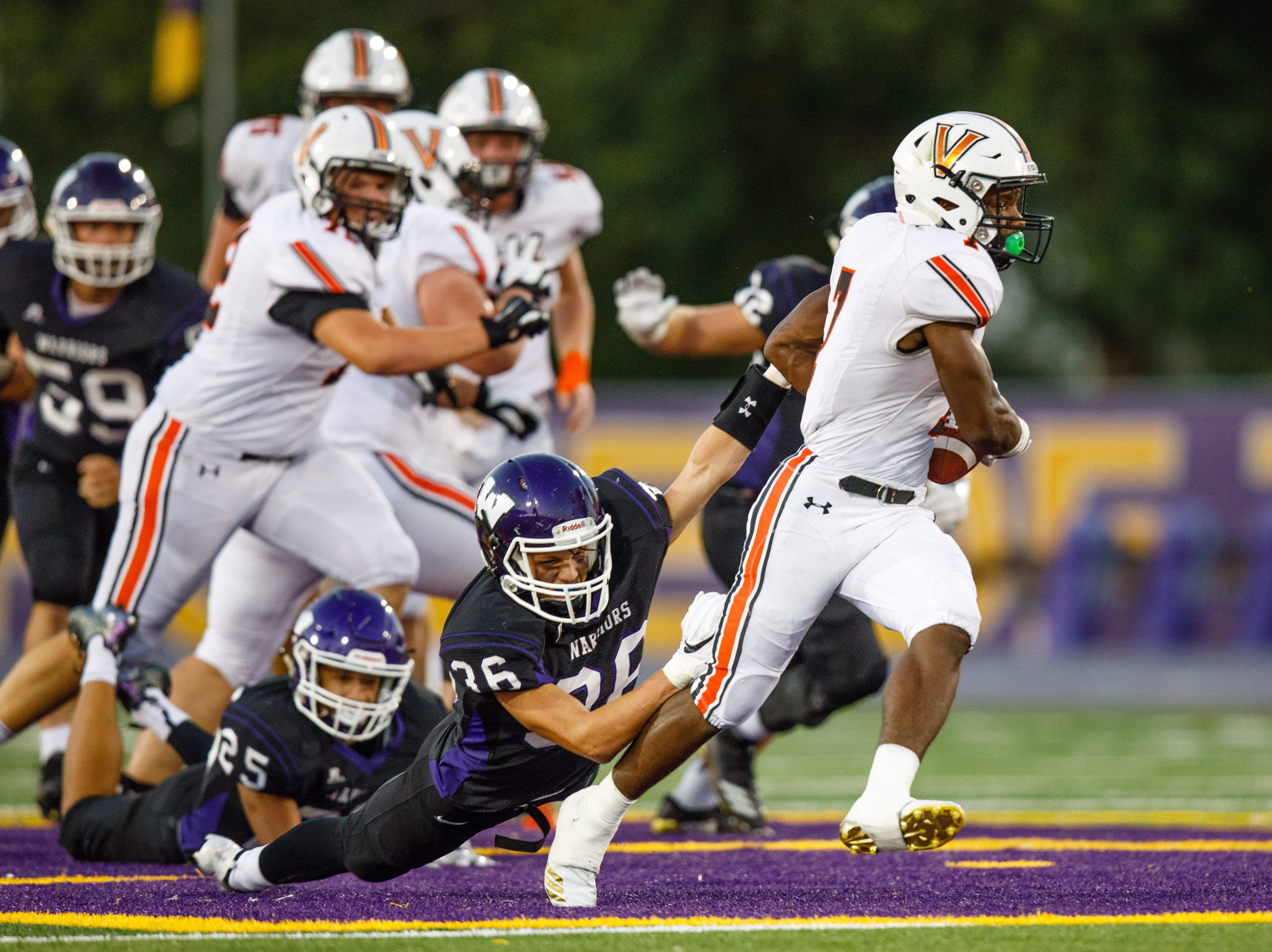 Valley High School's Tre Fugate (7) breaks a tackle by Waukee's Joe Morrison (36) in the first quarter Friday, Sept. 14, 2018, at Waukee Stadium.
