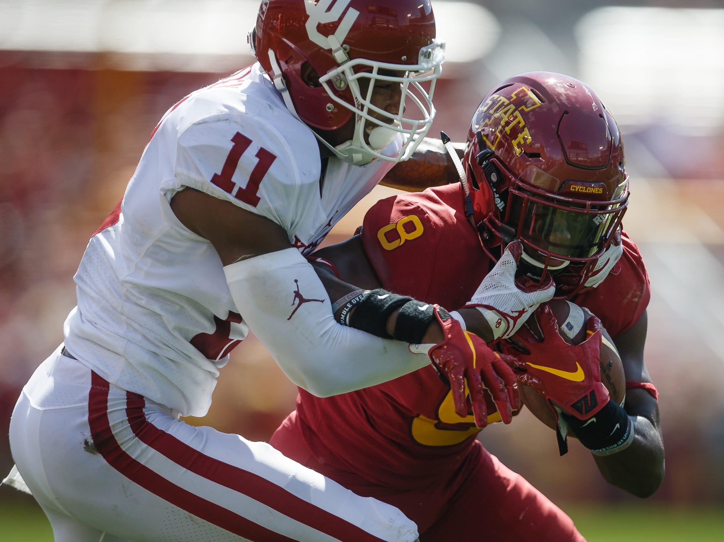 Iowa State's Deshaunte Jones (8) is tackled by Oklahoma's Parnell Motley (11) during their football game at Jack Trice Stadium on Saturday, Sept. 15, 2018 in Ames. Oklahoma would go on to win 37-27.