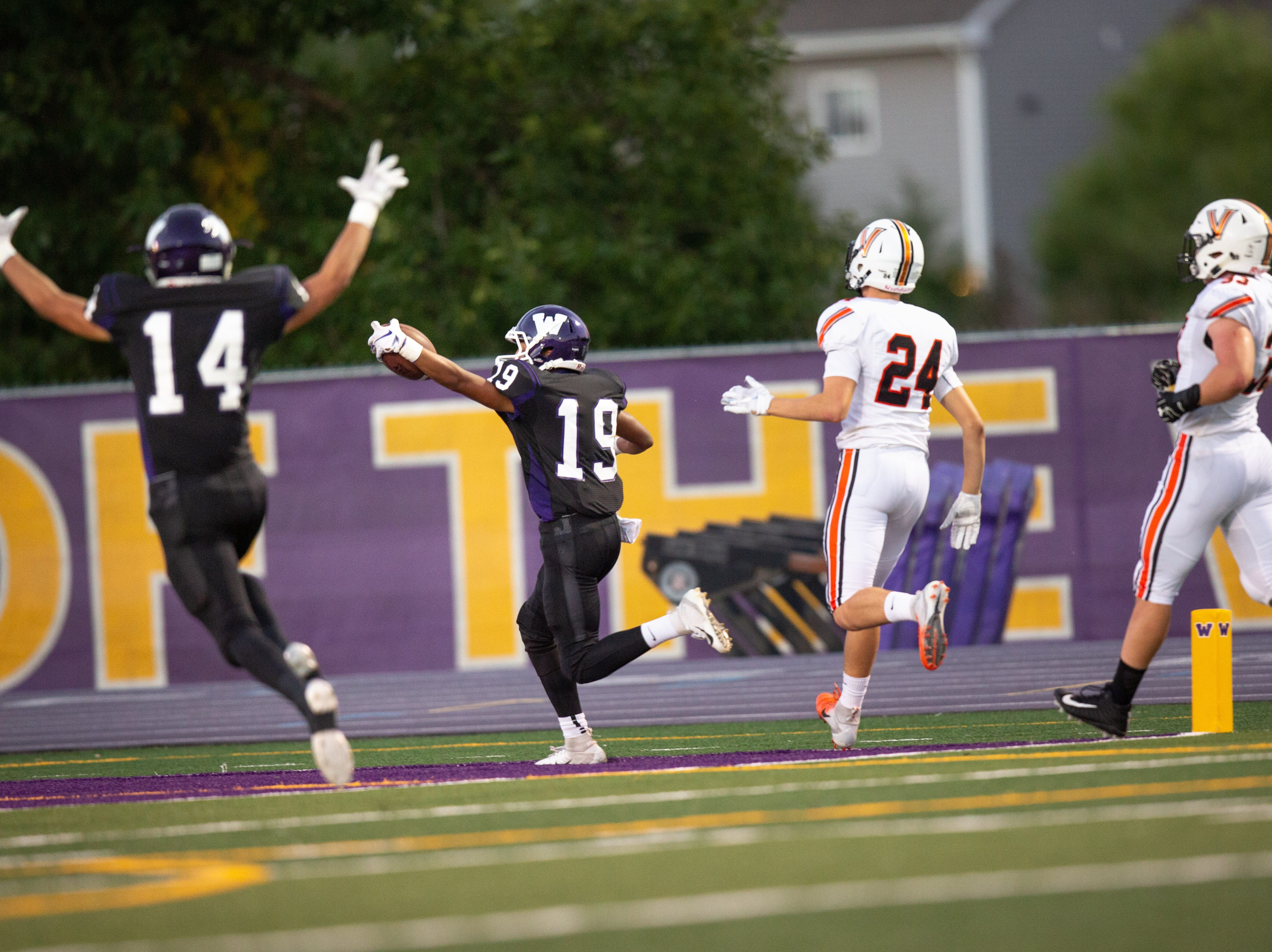 Waukee High School's Zach Gaines (19) runs into the end zone ahead of Valley's Drew Jirak (24) in the first quarter Friday, Sept. 14, 2018, at Waukee Stadium.