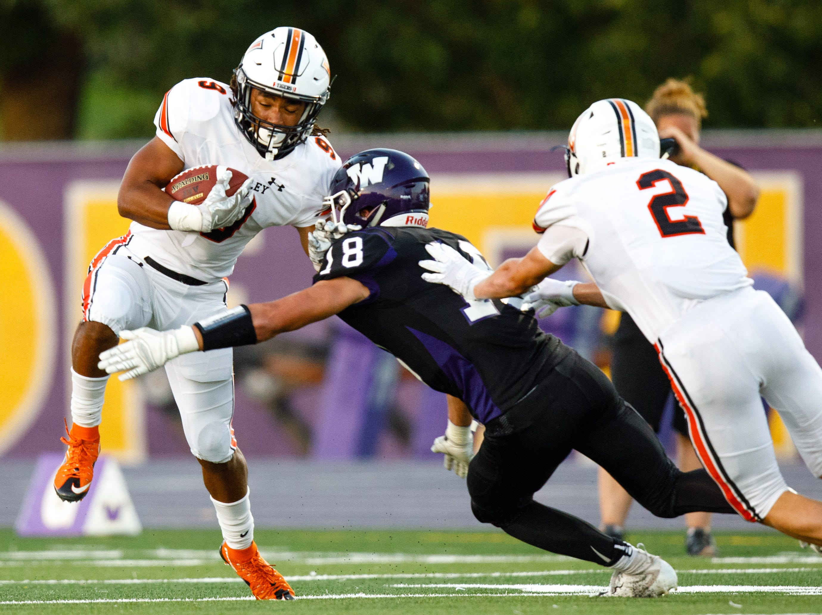 Valley High School's Creighton Mitchell (9) is hit by Waukee's Zach Eaton (18) after catching a pass in the first quarter Friday, Sept. 14, 2018, at Waukee Stadium.