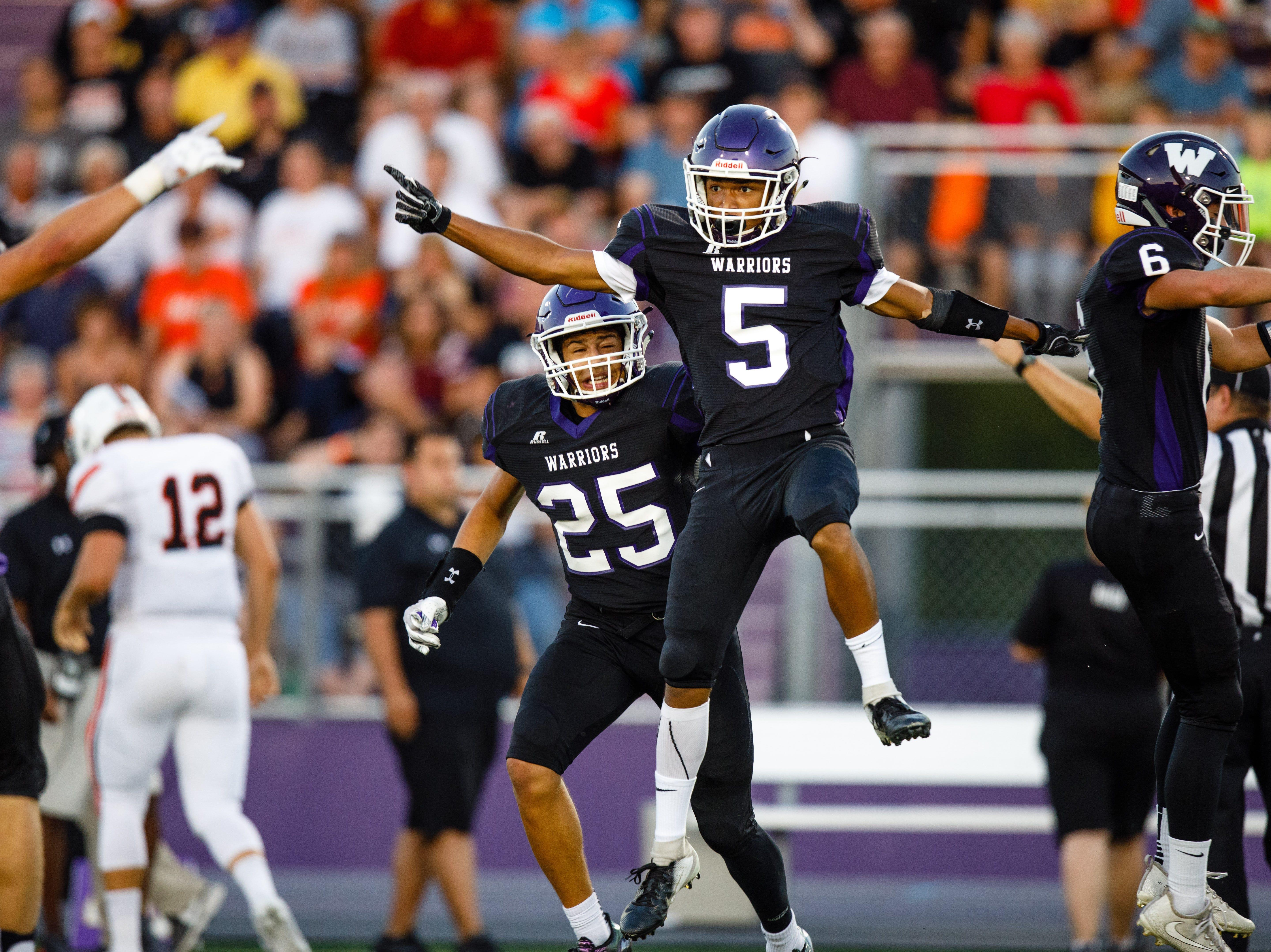 Waukee High School's Aaron Smith (5) celebrates an interception on Valley in the first quarter Friday, Sept. 14, 2018, at Waukee Stadium.