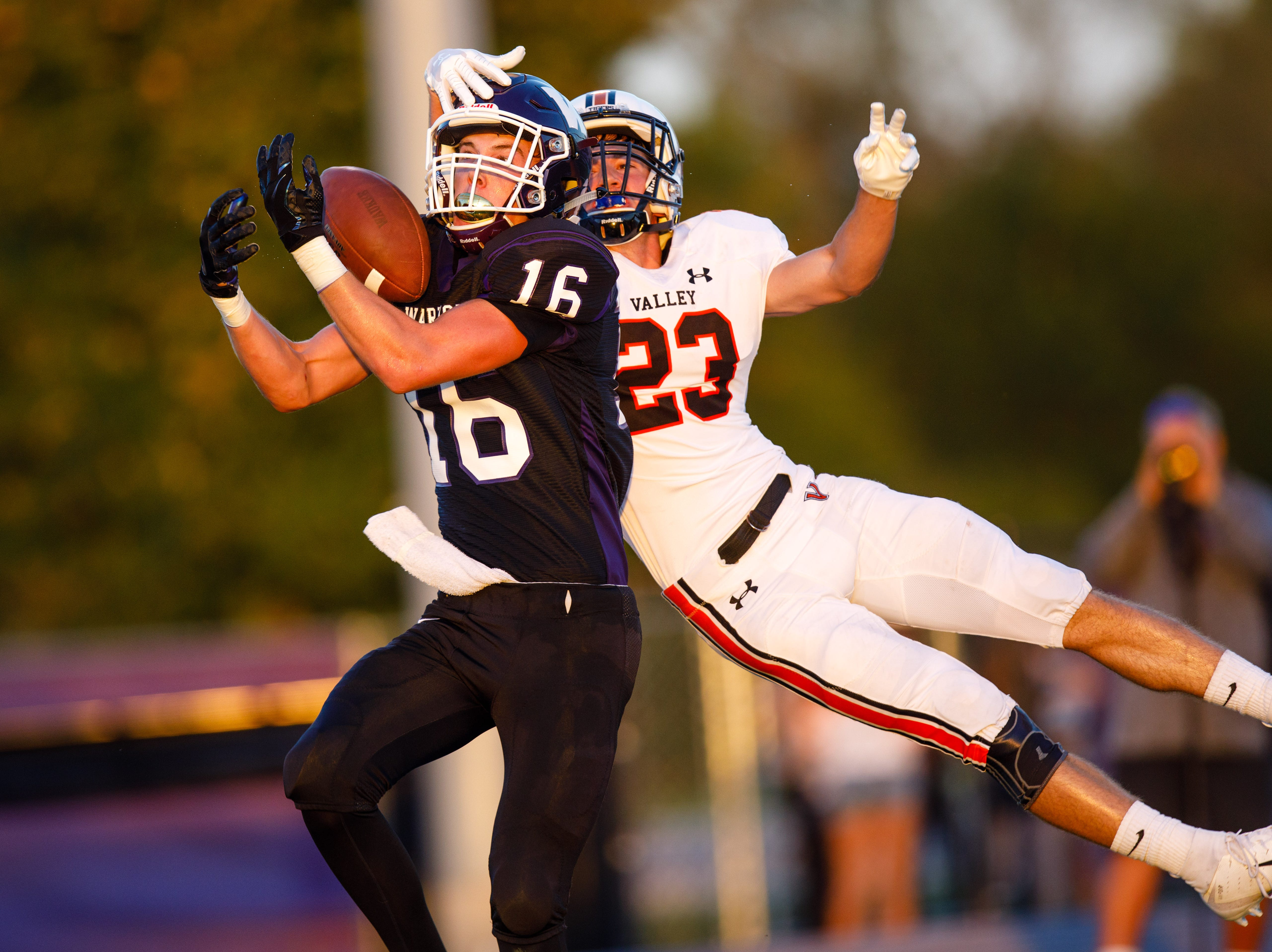 Waukee High School's Sam O'Dell (16) pulls in a pass ahead of Valley's Nathan Williams (23) in the first quarter Friday, Sept. 14, 2018, at Waukee Stadium.