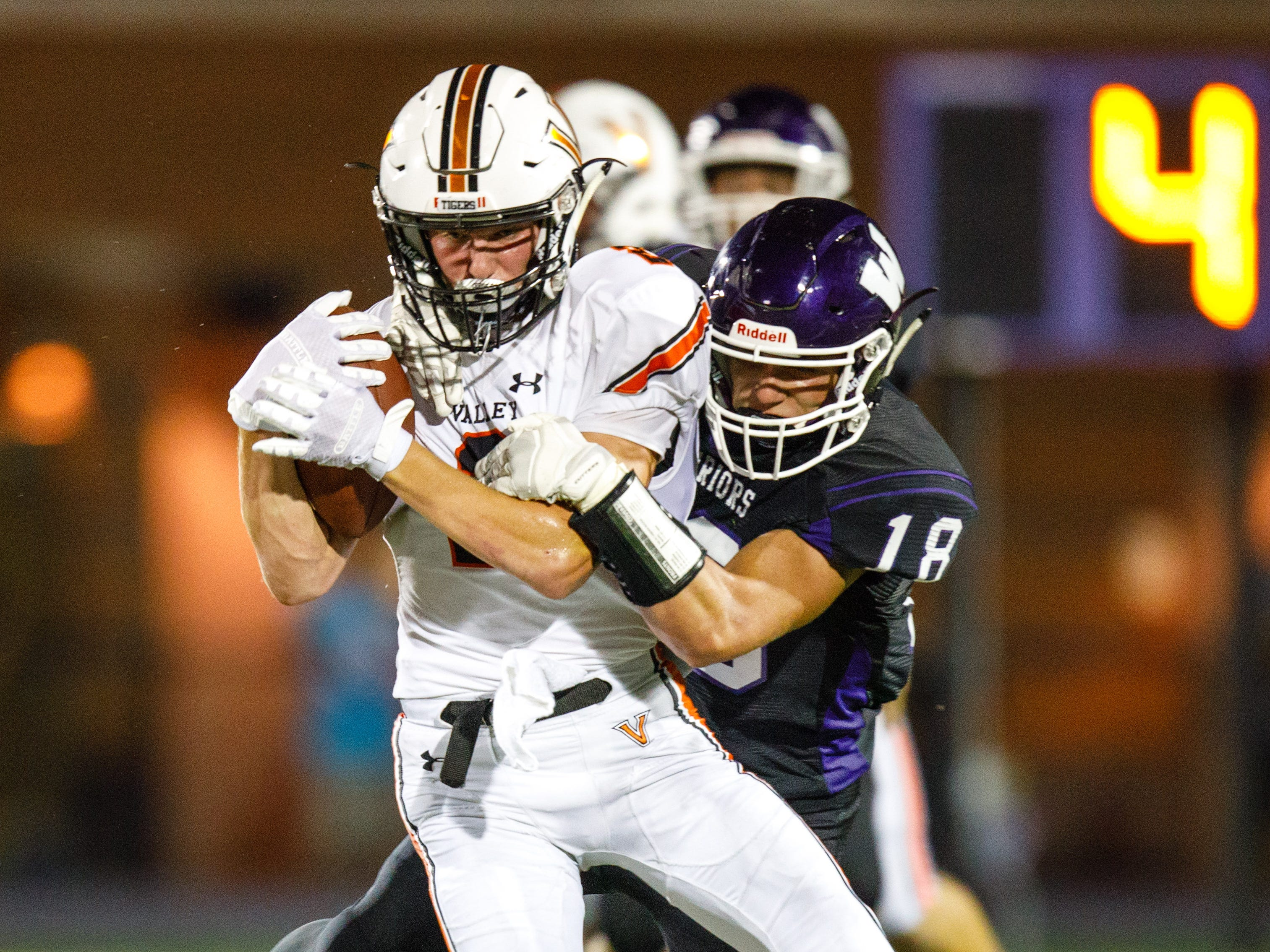 Valley High School's Ryan Neu (2) is hit by Waukee's Zach Eaton (18) in the second quarter Friday, Sept. 14, 2018, at Waukee Stadium.
