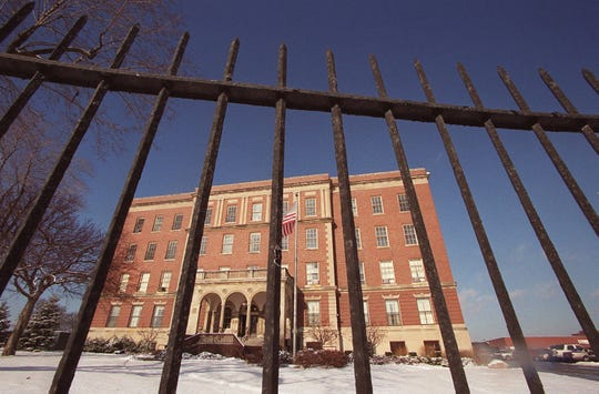An imposing metal fence stands in front of part of the Kay Beard Building in Westland in December 2000. The building is virtually all that's left of a complex that once numbered 55 buildings and was known as Eloise, Michigan.