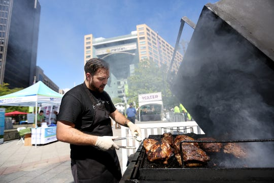Matt Romine, of Farm Field Table, smokes pork for the curried-rubbed pork, during the 2018 Detroit Free Press Wine & Food Experience at Campus Martius park in downtown Detroit on Saturday, Sept. 15, 2018.