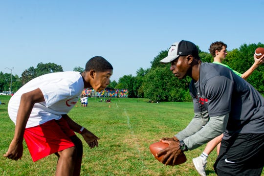 Former NFL player Tyrone Poole, right, faces off against Bryan Williams, 13, of Detroit, while running defensive back drills at  a football clinic at Balduck Park in Detroit on Saturday, Sept 15, 2018.
