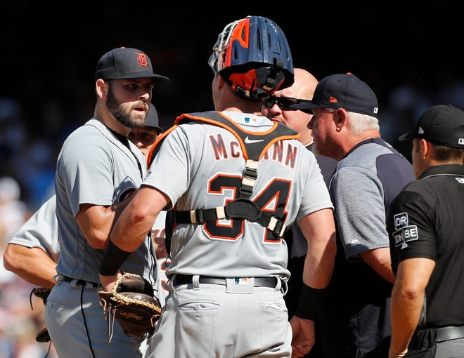 Michael Fulmer talks with catcher James McCann and manager Ron Gardenhire before leaving the game during the first inning Saturday.
