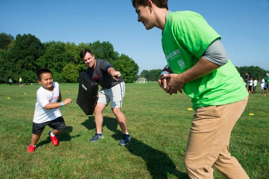 Toa Leaupepe, 6, of Detroit, left, is told by into former University of Connecticut coach Dave DeBoer of Grosse Pointe to grab the ball from volunteer Teddy Hilentzaris, 15, of Grosse Pointe Park during  a football clinic at Balduck Park in Detroit on Saturday, Sept 15, 2018.