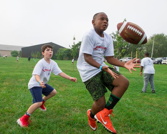 Micah Walker, 10, of Detroit, right, and Dylan Stringfellow, 9, of Grosse Pointe Park, play catch while waiting for a football clinic at Balduck Park in Detroit on Saturday, Sept 15, 2018.