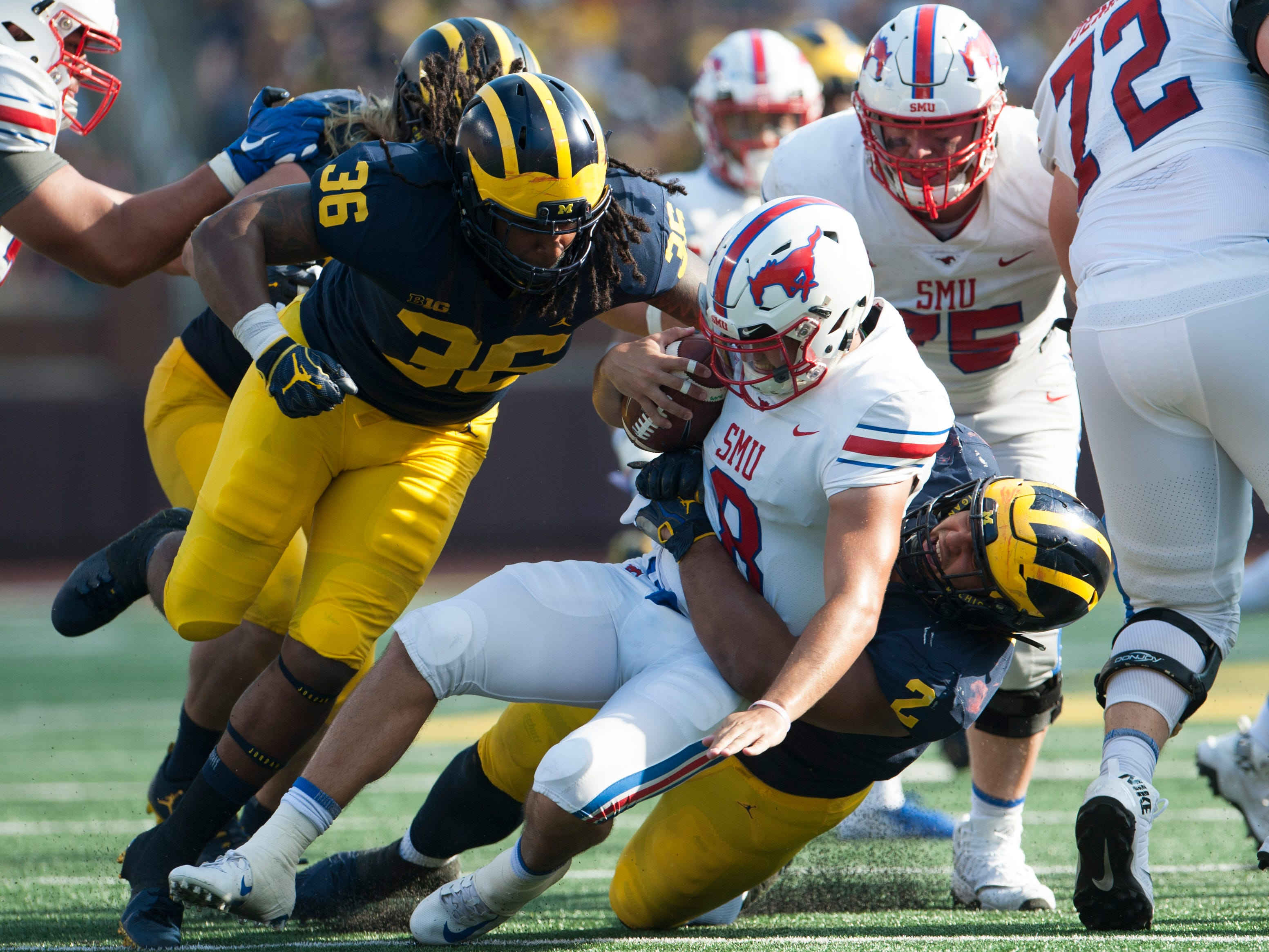 Michigan linebacker Devin Gil (36) and defensive lineman Carlo Kemp (2) sack Southern Methodist quarterback Ben Hicks in the second quarter.