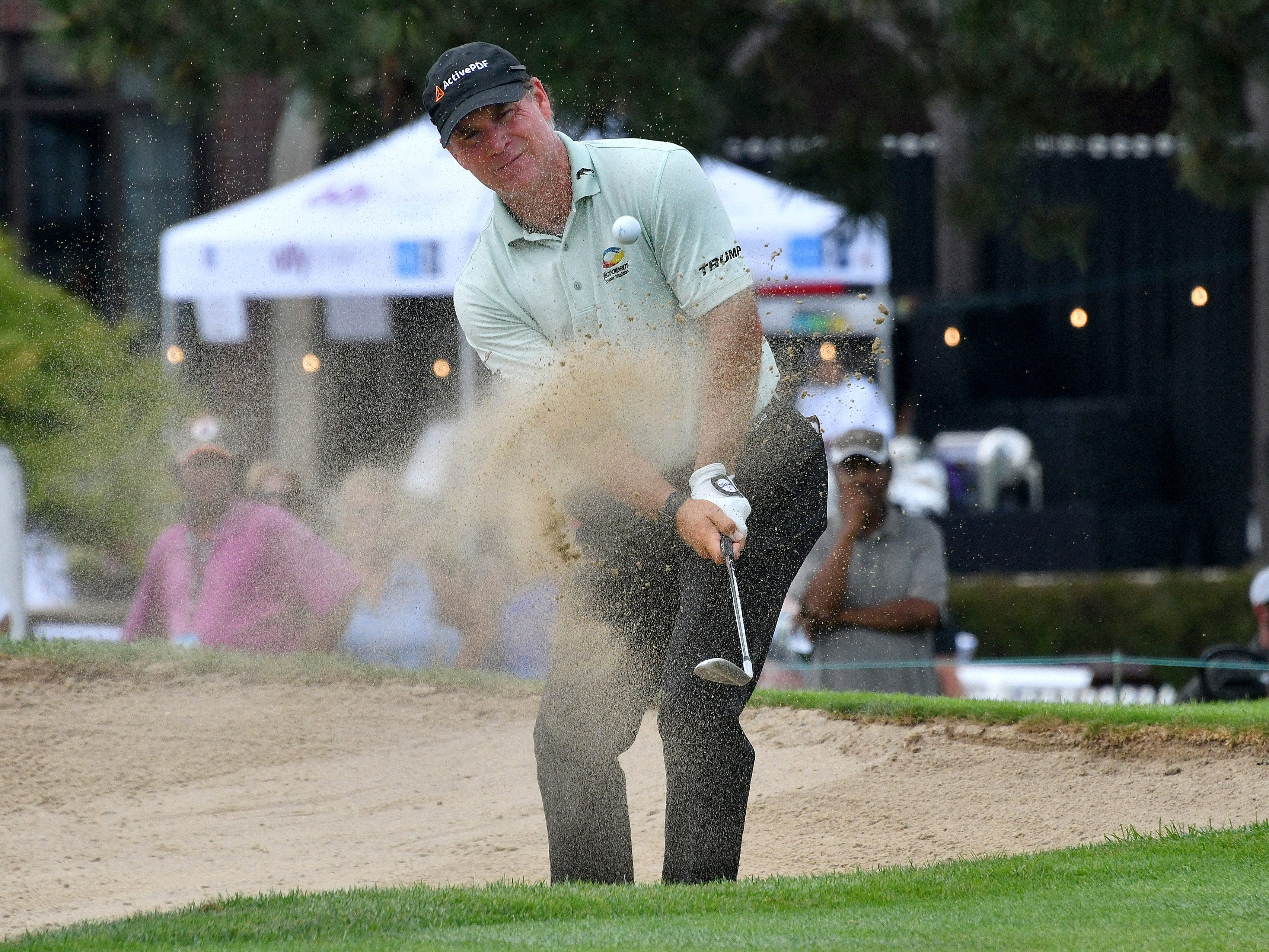 Scott McCarron watches his shot out of the sand on the ninth hole on day one.
