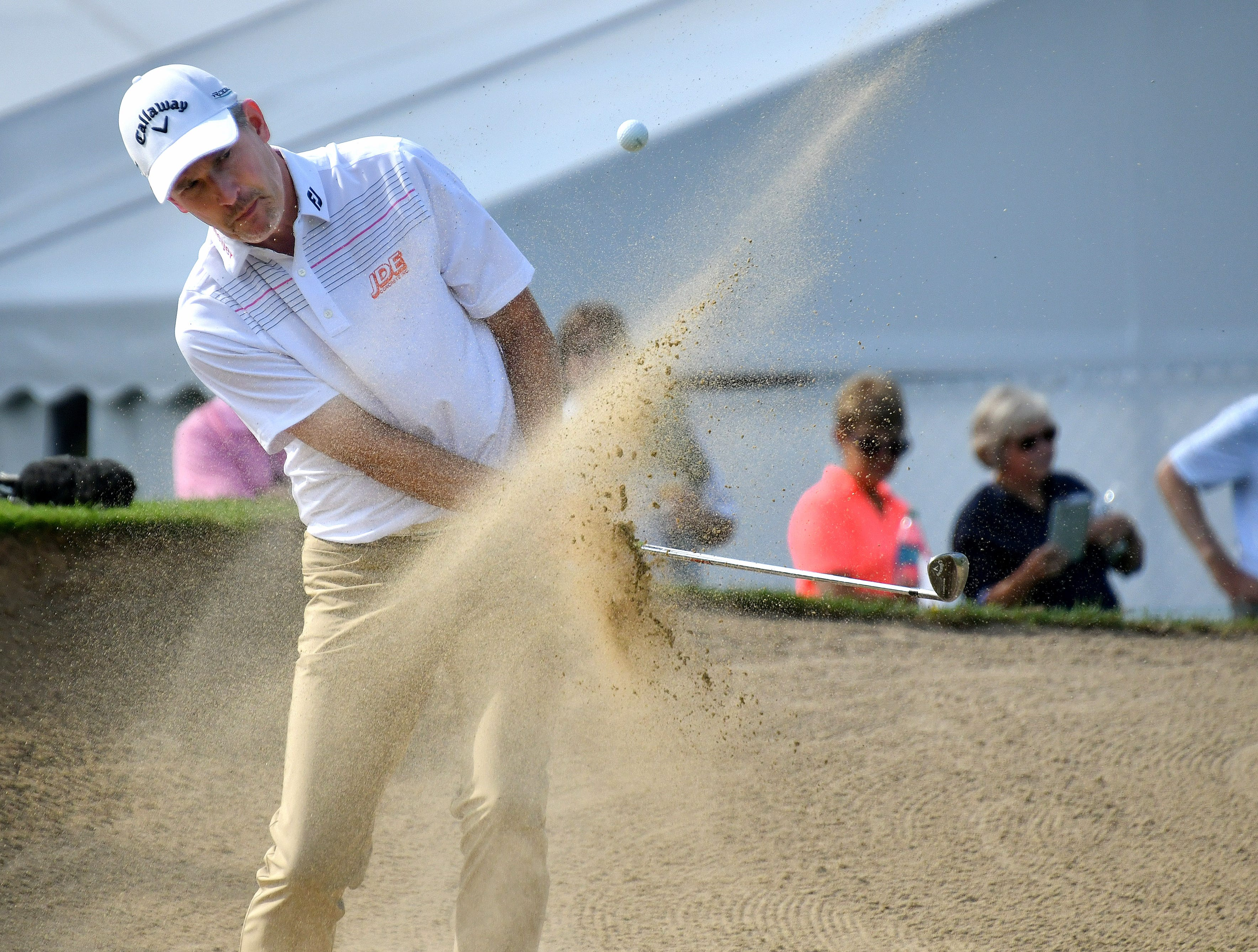 Grandville Michigan's Tom Werkmeister blasts out of the bunker on the ninth hole.