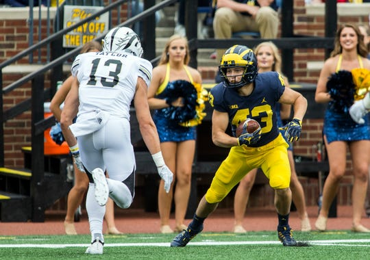 "Jake McCurry is one of three Michigan players who are helping to outfit youth football players in the Midwest with a non-profit organization called ""TUFF: The Uniform Funding Foundation."""