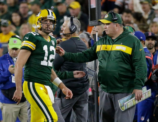 Green Bay Packers coach Mike McCarthy, right, looks at Aaron Rodgers as he walks off the field after injuring his leg in the season opener.