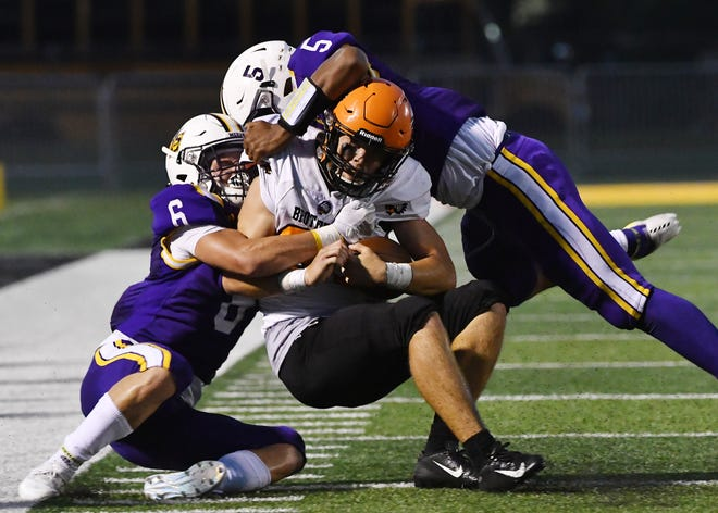De La Salle's Devin Campbell and Braden Babich bring down Brother Rice's James Donaldson in the second quarter.